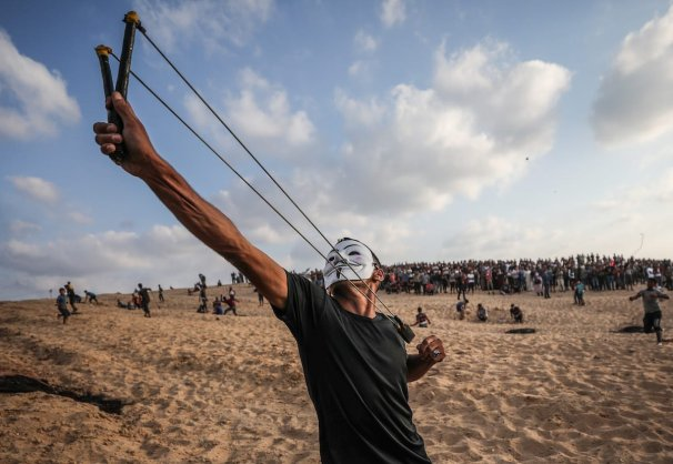 """GAZA CITY, GAZA - OCTOBER 8: Palestinians throw stones in response to Israeli forces' intervention as they gather to support the """"maritime demonstration"""" to break the Gaza blockade by sea with more than 20 vessels of various sizes in Gaza City, Gaza on October 8, 2018. ( Mustafa Hassona - Anadolu Agency )"""