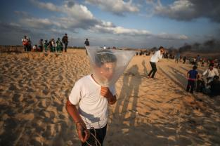 """GAZA CITY, GAZA - OCTOBER 8: A protester tries to protect himself with a nylon bag as Israeli soldiers intervene Palestinians with gas bomb as Palestinians gather to support the """"maritime demonstration"""" to break the Gaza blockade by sea with more than 20 vessels of various sizes in Gaza City, Gaza on October 8, 2018. ( Mustafa Hassona - Anadolu Agency )"""