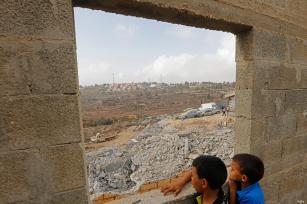 Palestinian children look at rubble left behind after Israeli forces demolished Palestinian owned buildings on 18 October 2018 [Wafa]