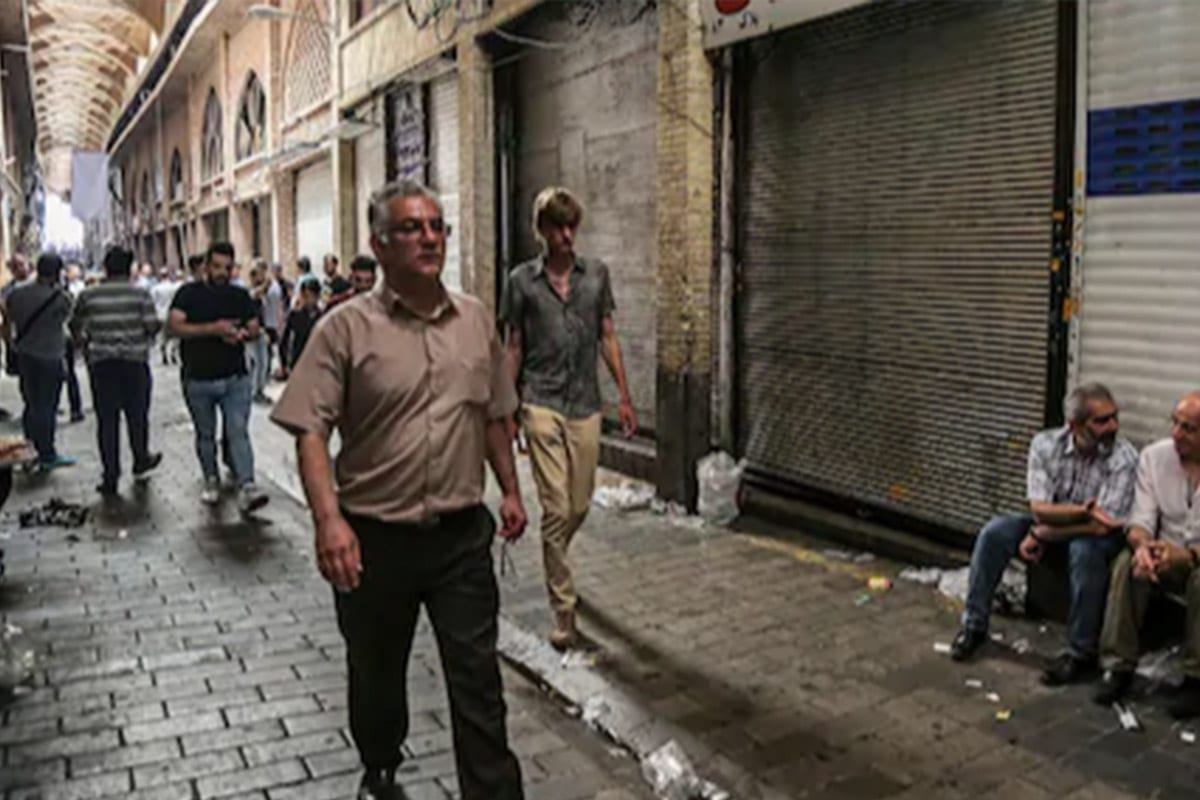 People walk through the old grand bazaar where shops are closed after a protest in Tehran, Iran [Twitter]