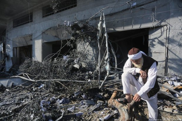 An elderly Palestinian man leans on a tree destroyed and tangled with debris outside a building. 13 November 2018 [Mohammed Asad/Middle East Monitor]