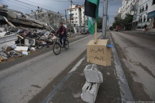 A man on his bike rides through the rubble and carnage with his shopping. 14 November 2018, Gaza [Mohammed Asad/Middle East Monitor]