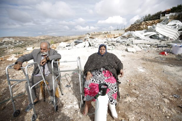 Palestinian Basma Al-Rajabi with her oxygen tube and her husband Muhammed Al-Rajabi are seen at their building's wreckage after Israeli forces demolished their house with the claim of being unlicensed in Beit Hanina town of Old City, East Jerusalem on 6 November, 2018 [Mostafa Alkharouf/Anadolu Agency]