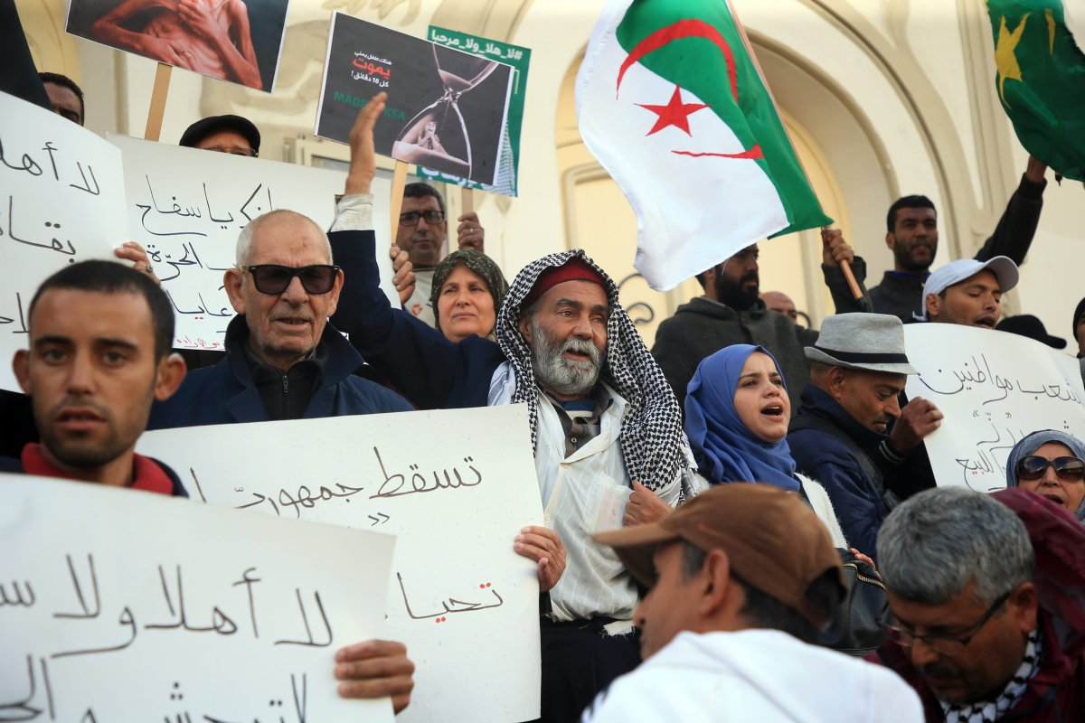 Tunisians hold up signs and flags as they protest against the expected visit of the Saudi Crown Prince to the country, in Habib Bourguiba Avenue in the capital Tunis, Tunisia on 27 November, 2018 [Yassine Gaidi/Anadolu Agency]