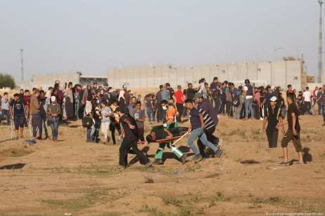Paramedics attend to an injured Palestinian who was hurt after Israeli forces attacked protesters at the Gaza-Israel border during the Great March of Return on 2 November 2018 [Middle East Monitor/Middle East Monitor]