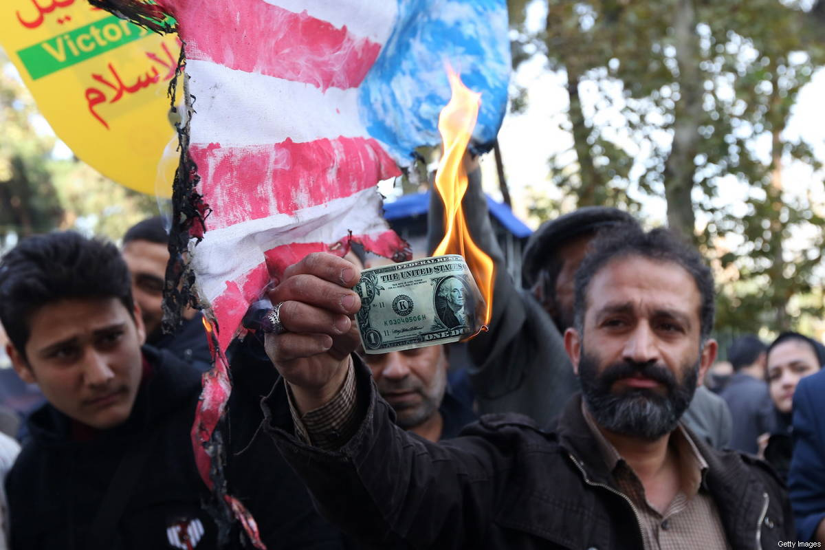 On the eve of the renewed sanctions by US, an Iranian protester burns a dollar banknote during a demonstration outside the former US embassy in the Iranian capital Tehran on 4 November 2018 [ATTA KENARE/AFP/Getty Images]