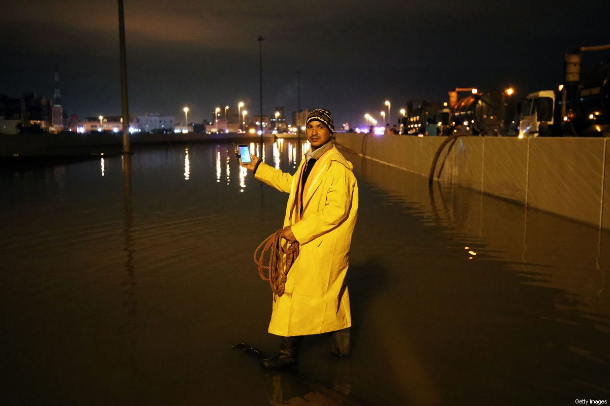 A Municipal worker poses with his smarthpne as his team works on draining water from a flooded underpass in al-Mangaf district, south of Kuwait City, on November 10, 2018 [YASSER AL-ZAYYAT/AFP/Getty Images]