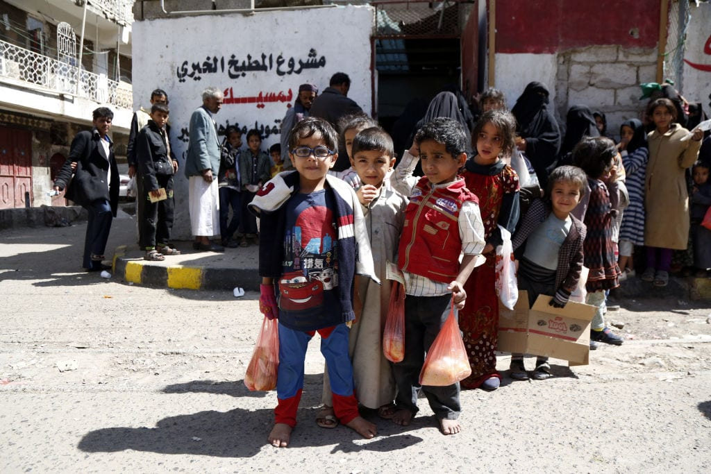 Yemeni children who were affected by the ongoing war carry free lunch meal they received from a charity food distribution center on November 03, 2018 in Sana'a, Yemen. [Mohammed Hamoud/Getty Images]