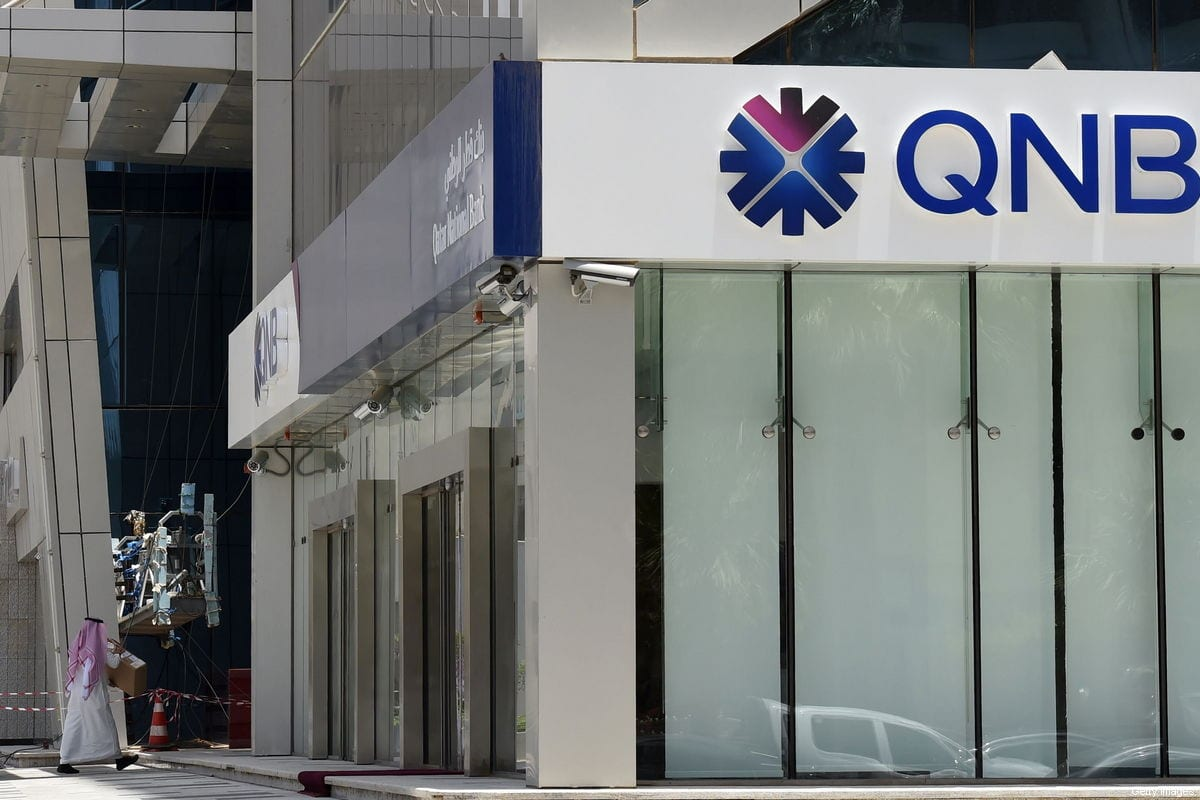 A picture taken on June 5, 2017 shows a man walking past the Qatar National Bank (QNB) branch in the Saudi capital Riyadh, following a severing of relations between major gulf states and gas-rich Qatar [FAYEZ NURELDINE/AFP/Getty Images]