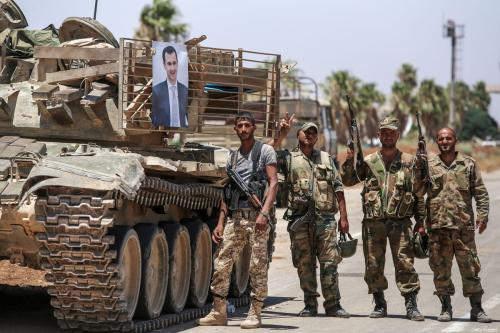 Syrian government soldiers stand flashing the victory gesture next to a picture of Syrian President Bashar al-Assad hanging on a tank at the Nassib border crossing with Jordan in the southern province of Daraa on July 7, 2018 [YOUSSEF KARWASHAN/AFP/Getty Images