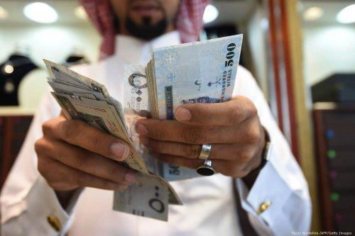 A man counts Saudi riyal banknotes at a market in Riyadh, Saudi Arabia on 3 October 2016 [Fayez Nurdeline /AFP/Getty Images]