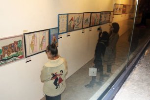 Guests look at the Palestinian tapestries on display at the P21 Gallery in London [Abdelrahman Said/Middle East Monitor]