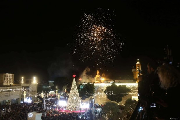 Palestinian Christians watch as fireworks light the sky to mark the lighting of the Christmas tree, in the biblical West Bank town of Bethlehem on 1 December 2018 [Ahmad Arouri/Apaimages]