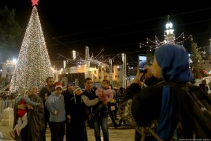 People pose for a photo in front of the illuminated Christmas Tree in Bethlehem on 1 December 2018. [Issam Rimawi /Anadolu Agency]