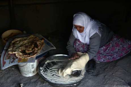 """A Palestinian woman bakes traditional bread """"Taboon"""" in the village of Salem east the West Bank City of Nablus, on 3 December 2018 [Shadi Jarar'ah/Apaimages]"""