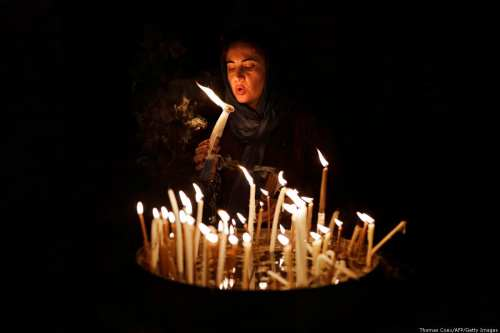 A Christian woman blows on candles inside the Church of the Holy Sepulchre in the Old City of Jerusalem, on 29 November, 2018 [Thomas Coex/AFP/Getty Images]