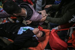 An injured Palestinian receives care after Israeli forces fire tear gas at protesters at the Gaza border on 14 December 2018 [Mohammed Asad/Middle East Monitor]