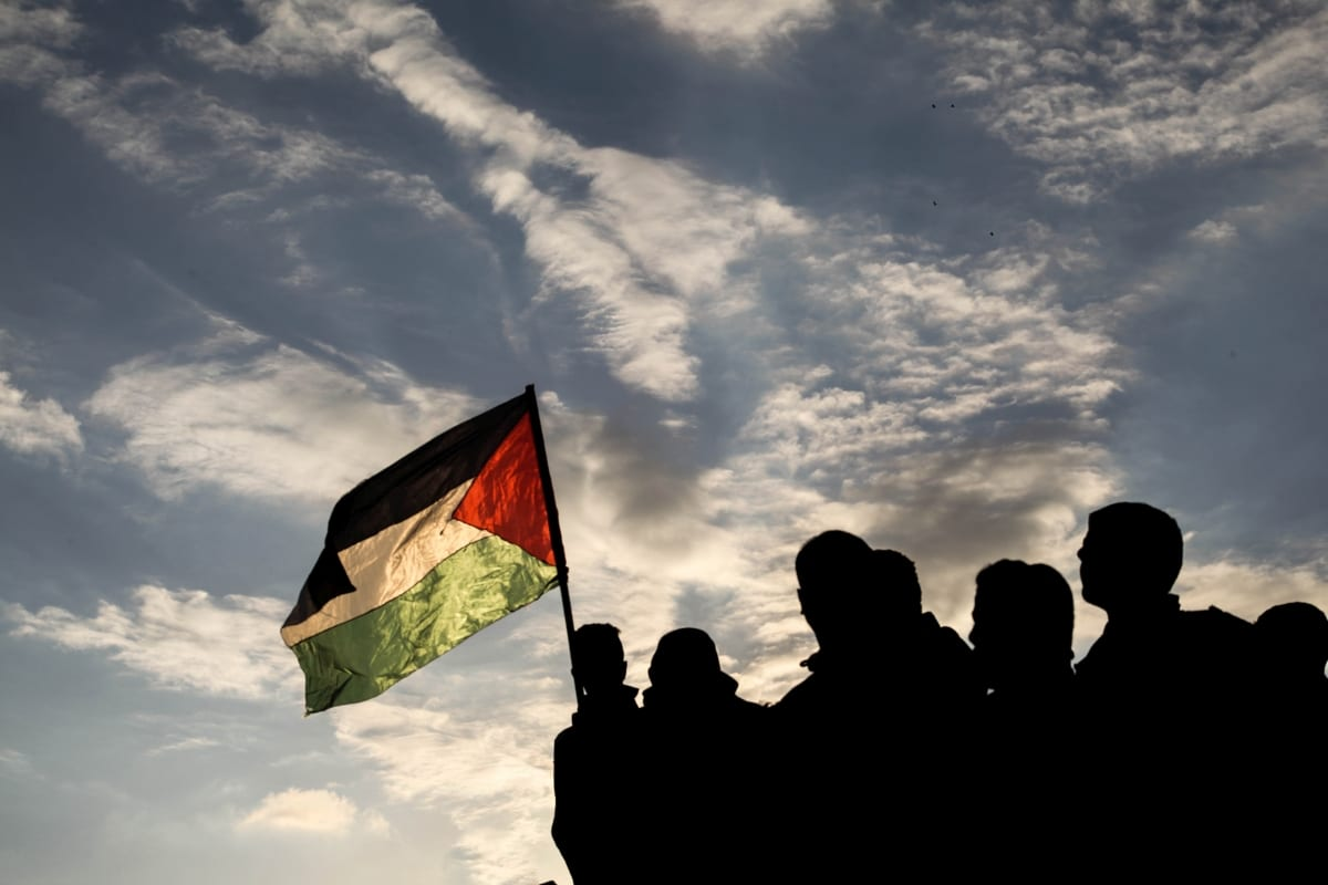 "A Palestinian holds a Palestinian flag during a protest within the ""Great March of Return"" demonstrations on the Israel-Gaza border near Jabalia Refugee Camp in Gaza City, Gaza on December 21, 2018. ( Ramez habboub - Anadolu Agency )"