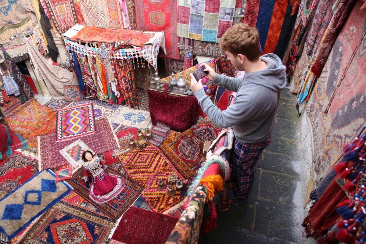 Tourist take photos of vibrant clothing shop in Turkey on 28 December 2018 [Behçet Alkan/Anadolu Agency]