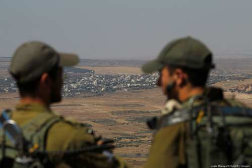 Israeli soldiers at an army base in the Israeli-annexed Syrian Golan Heights look out across the southwestern Syrian province of Quneitra, visible across the border on July 7, 2018. (Photo by JALAA MAREY/AFP/Getty Images)