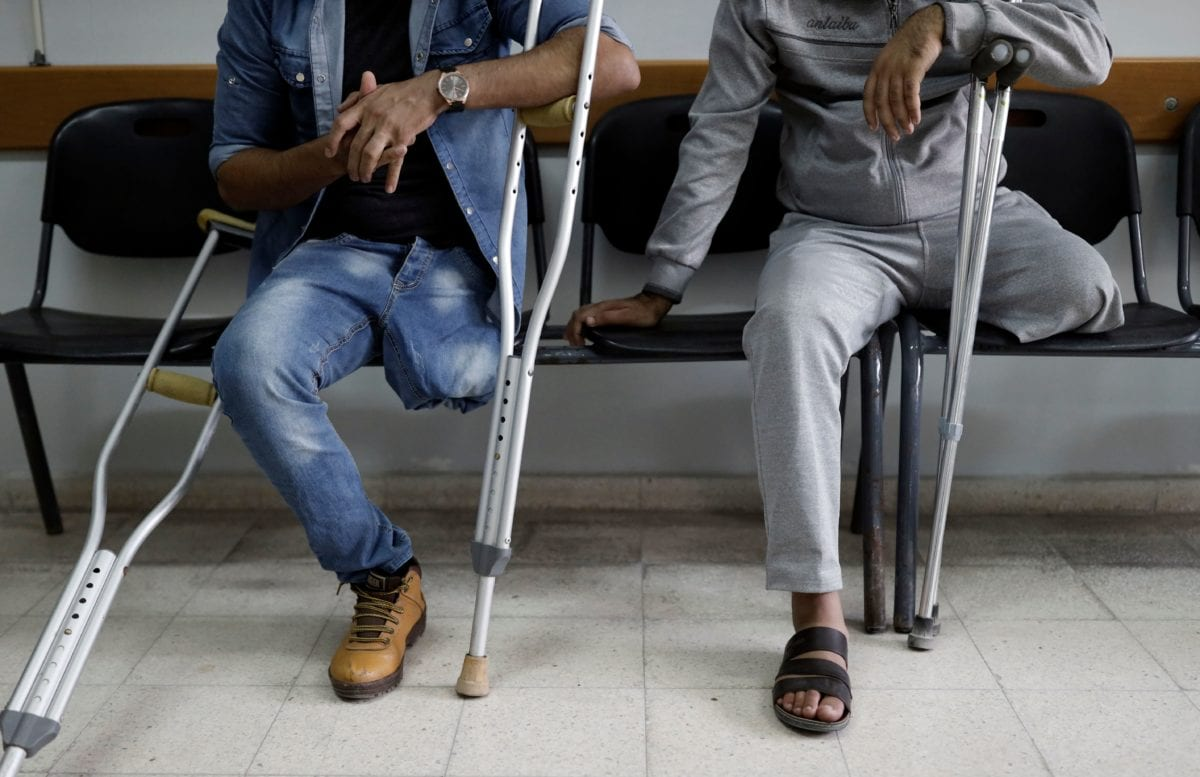 Two Palestinian amputee men sit in the waiting room at the ICRC for Artificial limbs and Polio Center (ALPC) in Gaza City on 25 October, 2018 [THOMAS COEX/AFP/Getty Images]