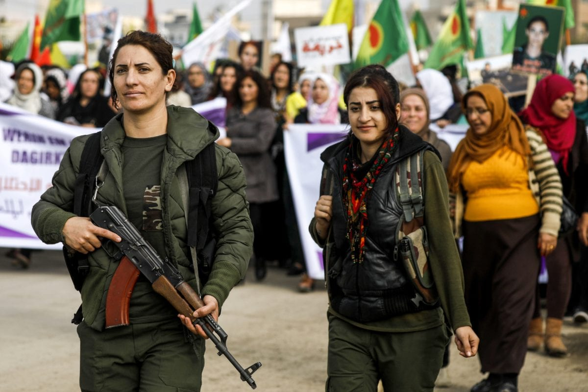 A Syrian Kurdish woman fighter holds a Kalashnikov assault rifle while marching with others during a demonstration in the northeastern Syrian city of Qamishli on November 25, 2018, as they mark the International Day for the Elimination of Violence against Women. (Photo by Delil souleiman / AFP) (Photo credit should read DELIL SOULEIMAN/AFP/Getty Images)