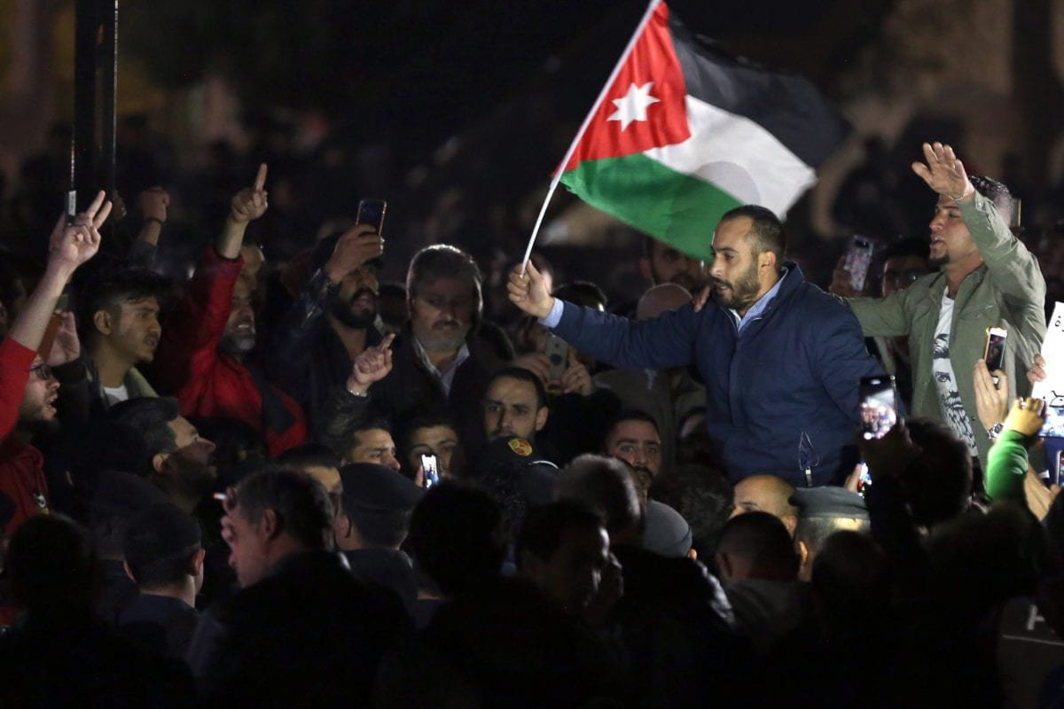 Jordanian protesters facing riot police chant slogans during a demonstration against the government's decision to raise taxes in the capital Amman on November 30, 2018 [KHALIL MAZRAAWI/AFP/Getty Images]