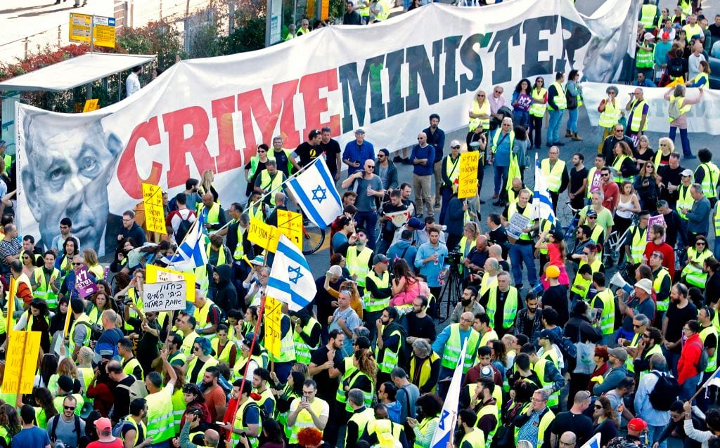 """Israelis wearing yellow vests, raise national flags and a banner showing Prime Minsiter Benjamin Netanyahu with a slogan that reads """"Crime Minsiter"""", demonstrate against the rising cost of living on December 14, 2018, in the Israeli coastal city of Tel Aviv. (Photo by JACK GUEZ/AFP/Getty Images)"""
