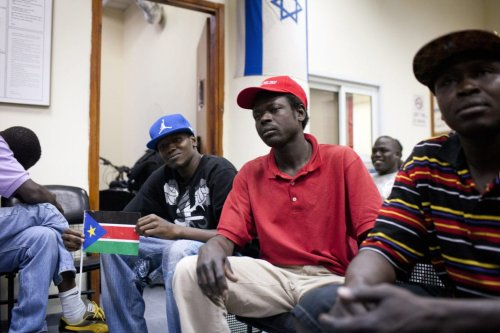 A South Sudanese refugee holds up his national flag as he is held alongside other refugees at a detention centre in Holon, south of Tel Aviv, on 11 June 2012. [OREN ZIV/AFP/GettyImages]