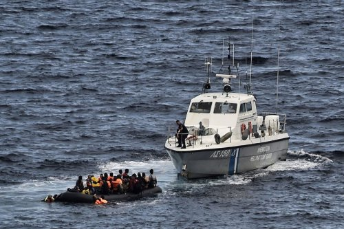 A Hellenic coast guard rescues refugees and migrants on a dinghy as they try to reach the Greek island of Lesbos while crossing the Aegean sea from Turkey on September 29, 2015 [ARIS MESSINIS/AFP/Getty Images]