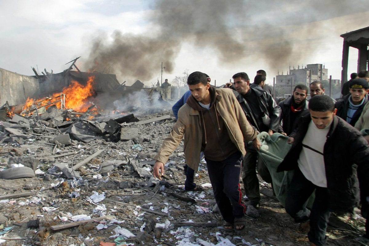 Fire and smoke rise from a destroyed building as Palestinians carry a victim of an Israeli air strike that targeted Buriej refugee camp in the central Gaza Strip on December 27, 2008. The Israeli air strike was part of it's 'Operation Cast Lead' offensive on Gaza. [YASSER SAYMEH/AFP/Getty Images]