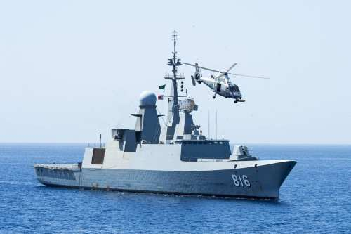 """The Royal Saudi Navy frigate Al Dammam (816) maneuvers into position, with its embarked AS565 SA Dauphin helicopter circling overhead, during exercise """"Eager Lion 2014"""" in the Gulf of Aden on May 28, 2014 [US Navy / Public Domain]"""