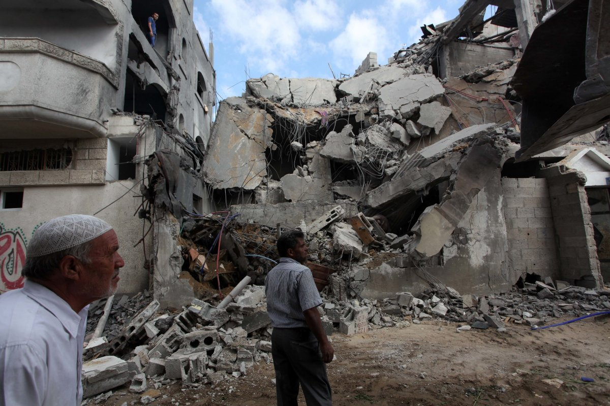 A Palestinian man outside his home after it was destroyed in air strike carried out by Israeli forces in Gaza on 9 August 2014 [Ashraf Amra/Apaimages]