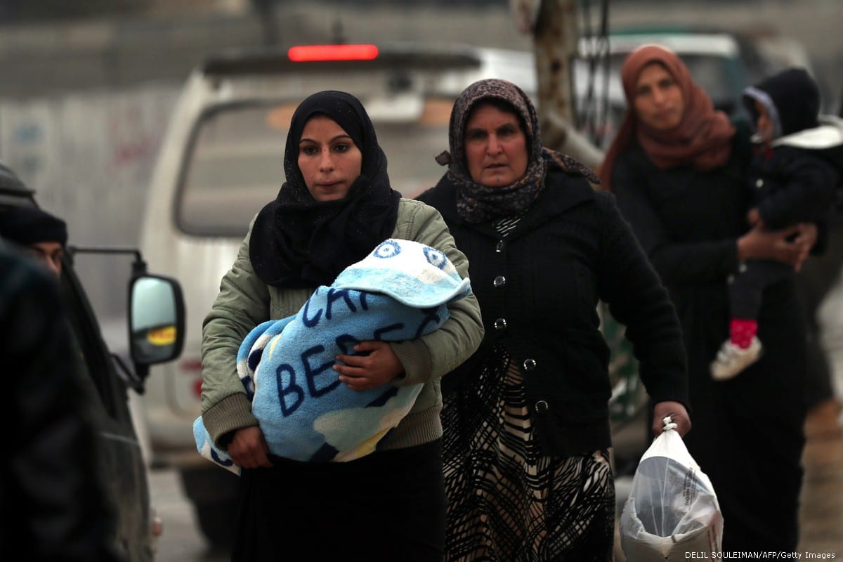 Syrians women carry children along the Turkish border on 30 December 2018 [DELIL SOULEIMAN/AFP/Getty Images]