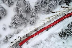 A drone photo shows about 3,000 people holding a giant Turkish flag attend a march at Sis Mountain foothill held to commemorate the martyrs of the World War I Battle of Sarikamis, on January 06, 2019 at Salpazari district of Trabzon, Turkey [Hakan Burak Altunöz / Anadolu Agency]