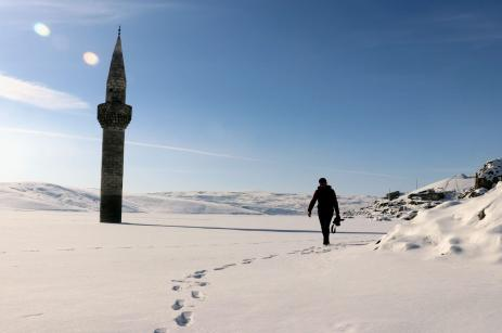 A man walks towards a minaret on snow after submerged area froze in Bascavus village of Agri, Turkey on January 19, 2019. [Sıtkı Yıldız/Anadolu Agency]