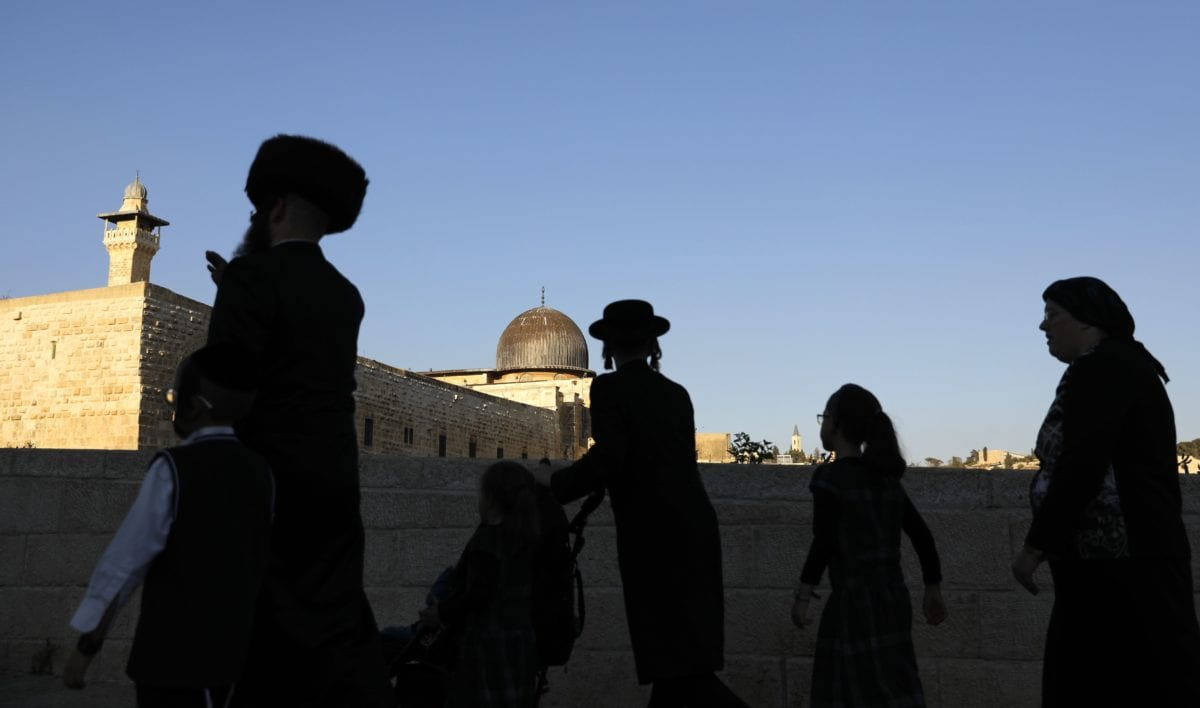 Members of an Ultra-Orthodox Jewish family walk at the Jewish quarter in Jerusalem's Old City overlooking al-Aqsa Mosque on September 27, 2018 -(Photo by AHMAD GHARABLI/AFP/Getty Images)