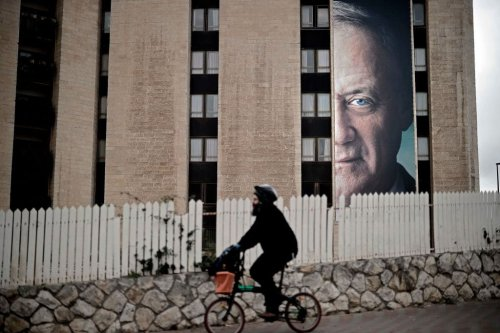A man rides a bycicle past a political campaign poster of former Israeli chief of staff Benny Gantz, in Jerusalem, on 28 January 2019. [THOMAS COEX/AFP/Getty Images]
