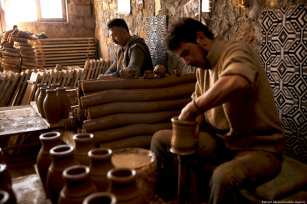 """Turkish craftsmen Yenal Yorgun (front) and Mustafa Alkan (rear) make clay pots. Yorgun and Alkan use the red clay collected from Kizilirmak (""""red river"""") and sell their finish products to Saudi Arabia, Dubai, Qatar in Cappadocia's Avanos district, Nevsehir, Turkey on 5 February 2019 [Behçet Alkan/Anadolu Agency]"""