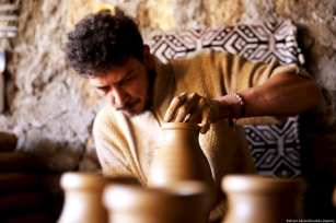 Turkish craftsmen Yenal Yorgun and Mustafa Alkan (not seen) make clay pots in Cappadocia's Avanos district, Nevsehir, Turkey on 5 February 2019 [Behçet Alkan/Anadolu Agency]