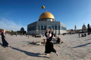 A picture taken with a fisheye lens shows a Palestinian girl playing with a football at the Al-Aqsa Mosque compound during a ceremony commemorating the Prophet Mohammed's ascent to heaven, known in Arabic as Isra and Miraj in the Old City of Jerusalem on 24 April 2017 [Mahmud Hams/AFP/Getty Images]