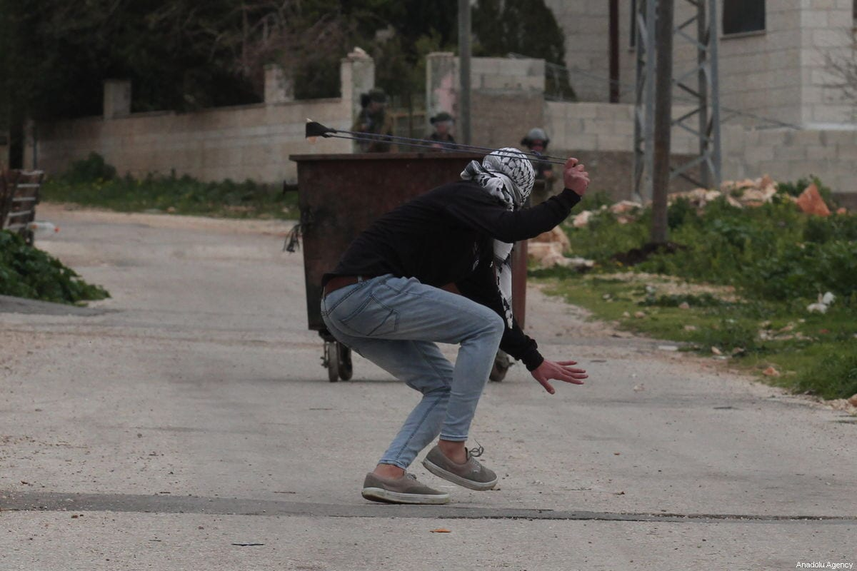 A Palestinians protestor hurls a rock towards Israeli forces, who fired tear gas and rubber bullets at them, during a protest against building of illegal settlements at the Kafr Qaddum village of Nablus, West Bank on February 01, 2019 [Nedal Eshtayah / Anadolu Agency]