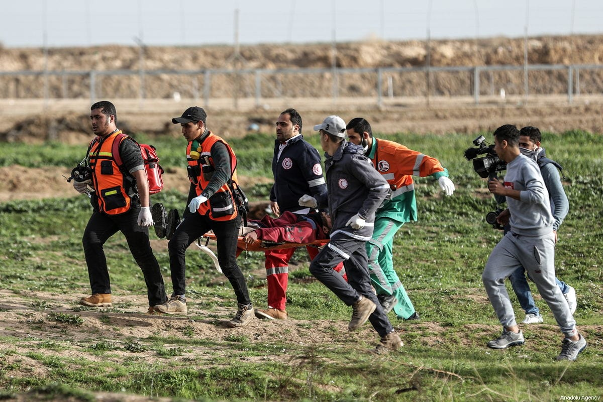 "Palestinian paramedics carry an injured man after Israeli security forces clashed with Palestinians protesting in a ""Great March of Return"" demonstration in Shuja'iyya neighborhood of Gaza City, Gaza on February 01, 2019 [Ali Jadallah / Anadolu Agency]"