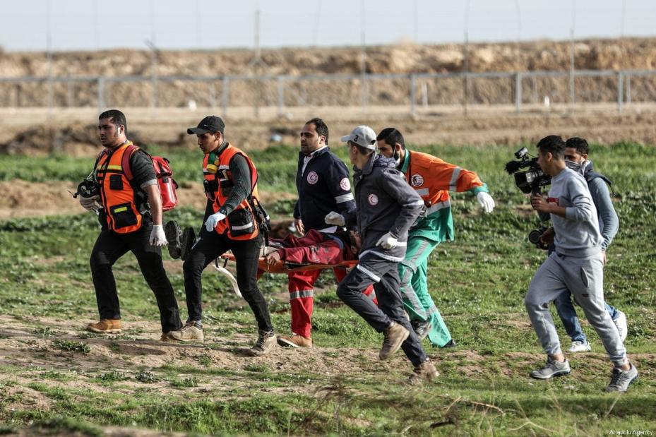 """Palestinian paramedics carry an injured man after Israeli security forces clashed with Palestinians protesting in a """"Great March of Return"""" demonstration in Shuja'iyya neighborhood of Gaza City, Gaza on February 01, 2019 [Ali Jadallah / Anadolu Agency]"""