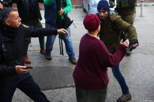 A Jewish settler reacts to members of the Palestinian Youth Against Settlements (YAS) activists as they gather in Hebron, West Bank on February 10, 2019. The YAS activists have dressed up similar to the Temporary International Presence in Hebron (TIPH), established after a massacre of Palestinians in 1994, following Israel's decision not to renew the mandate of the monitoring group in West Bank city [Mamoun Wazwaz / Anadolu Agency]