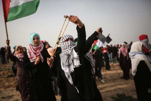"""Palestinian women use slingshot to throw stones to Israeli forces during Israeli forces' intervention to """"Great March of Return"""" demonstration near Al Bureij Refugee Camp in Gaza on February 15, 2019. ( Hassan Jedi - Anadolu Agency )"""