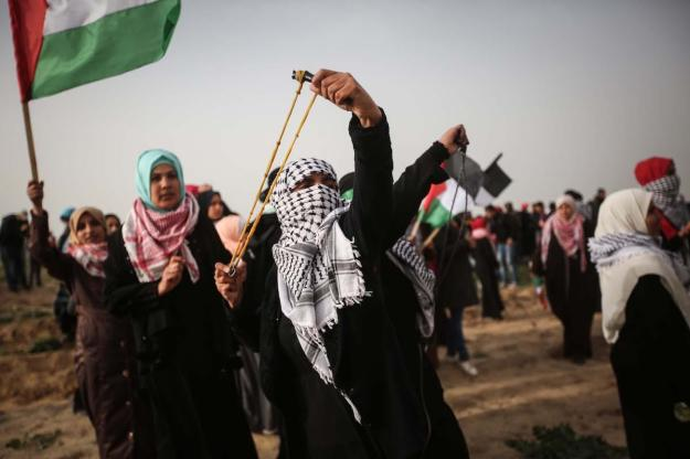 "Palestinian women use slingshot to throw stones to Israeli forces during Israeli forces' intervention to ""Great March of Return"" demonstration near Al Bureij Refugee Camp in Gaza on February 15, 2019. ( Hassan Jedi - Anadolu Agency )"
