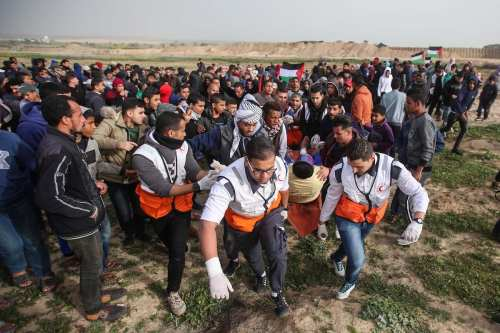 "Palestinian who was injured after Israeli forces fired on him, is being evacuated by health crews during ""Great March of Return"" demonstration near Al Bureij Refugee Camp in Gaza on February 15, 2019. ( Hassan Jedi - Anadolu Agency )"