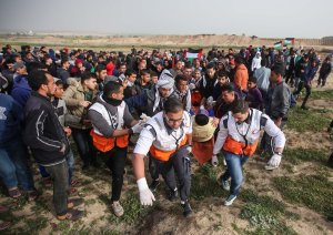 """Palestinian who was injured after Israeli forces fired on him, is being evacuated by health crews during """"Great March of Return"""" demonstration near Al Bureij Refugee Camp in Gaza on February 15, 2019. ( Hassan Jedi - Anadolu Agency )"""