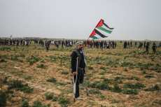 """A Palestinian man stands with a Palestinian flag as Israeli forces intervene demonstrators during a """"Great March of Return"""" demonstration at Huzaa district of Khan Yunis, Gaza on February 15, 2019. ( Mustafa Hassona - Anadolu Agency )"""